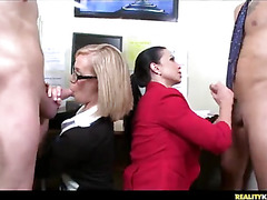 The girls are jacking the guys off and then they give them blowjobs on the desk in the office.